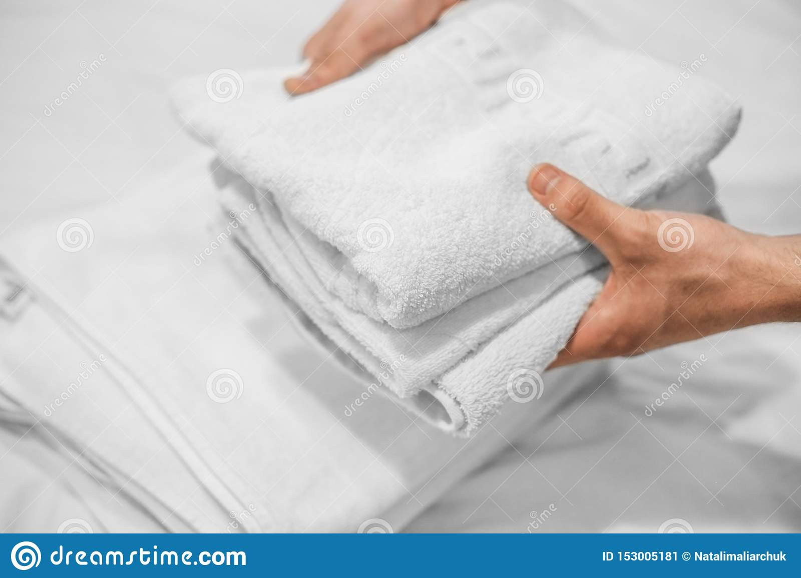 Hands put white towels on a white bed. Hotel business