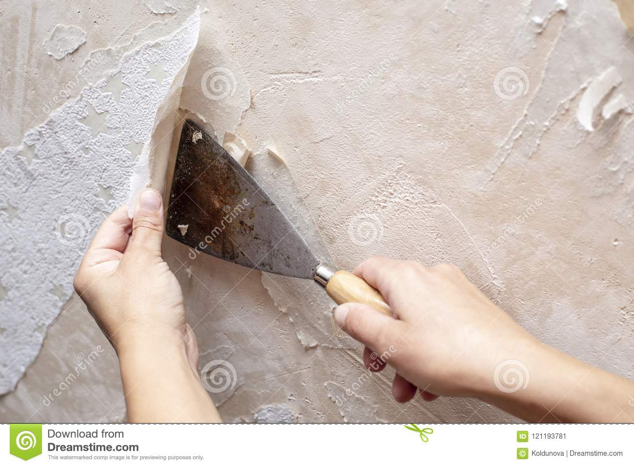 Hands Removing Old Wallpaper With The Help Of A Spatula During T