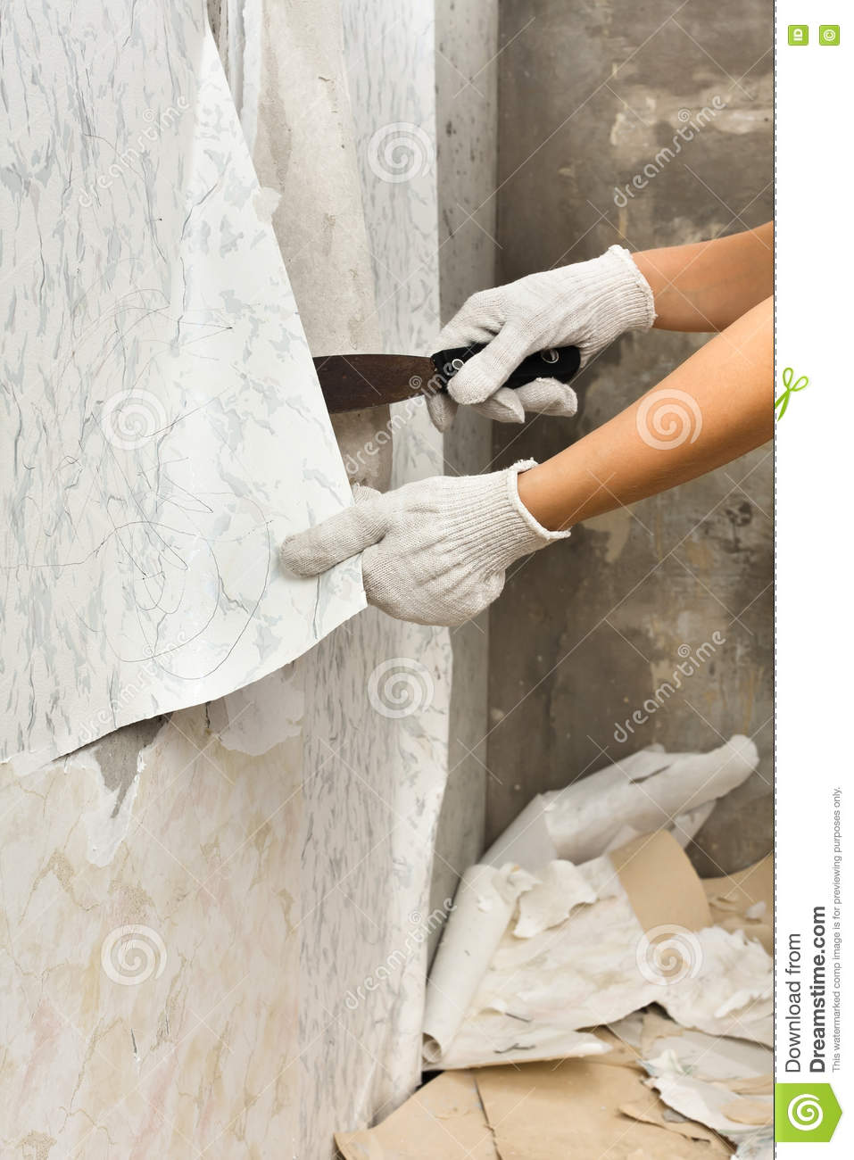 Hands Removing Old Wallpaper From Wall