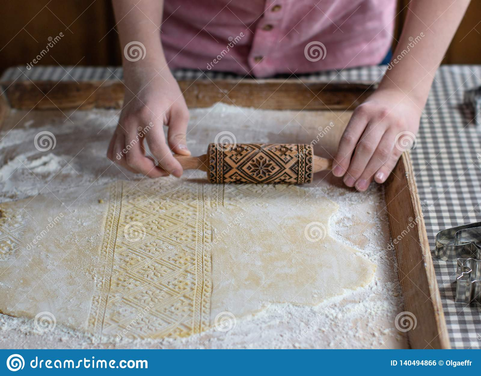 Hands rolling dough with an embossing rolling pin, on a wooden background
