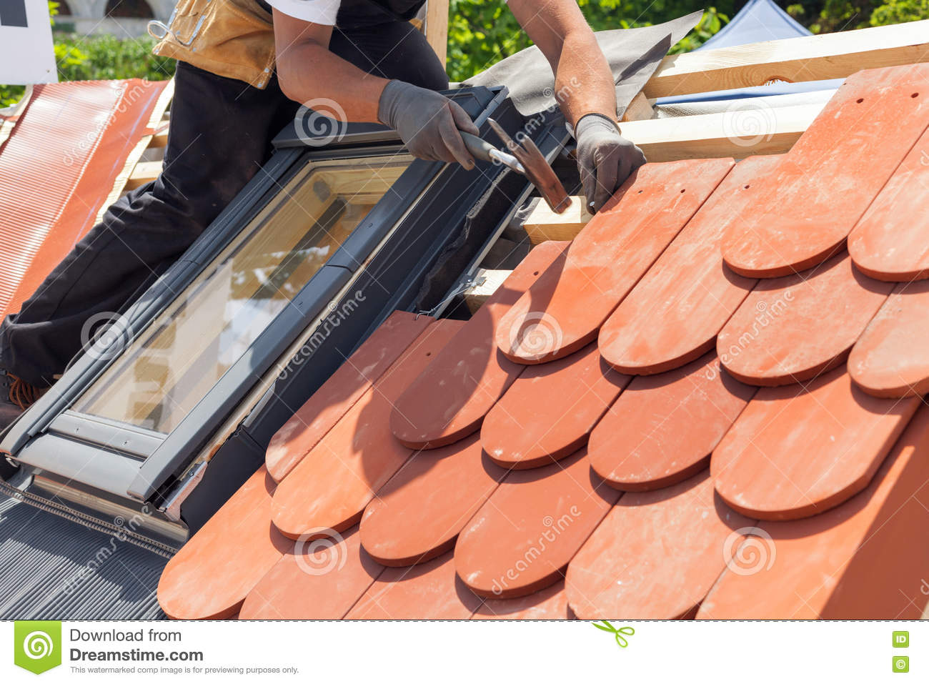 Hands of roofer laying tile on the roof. Installing natural red tile using hammer.