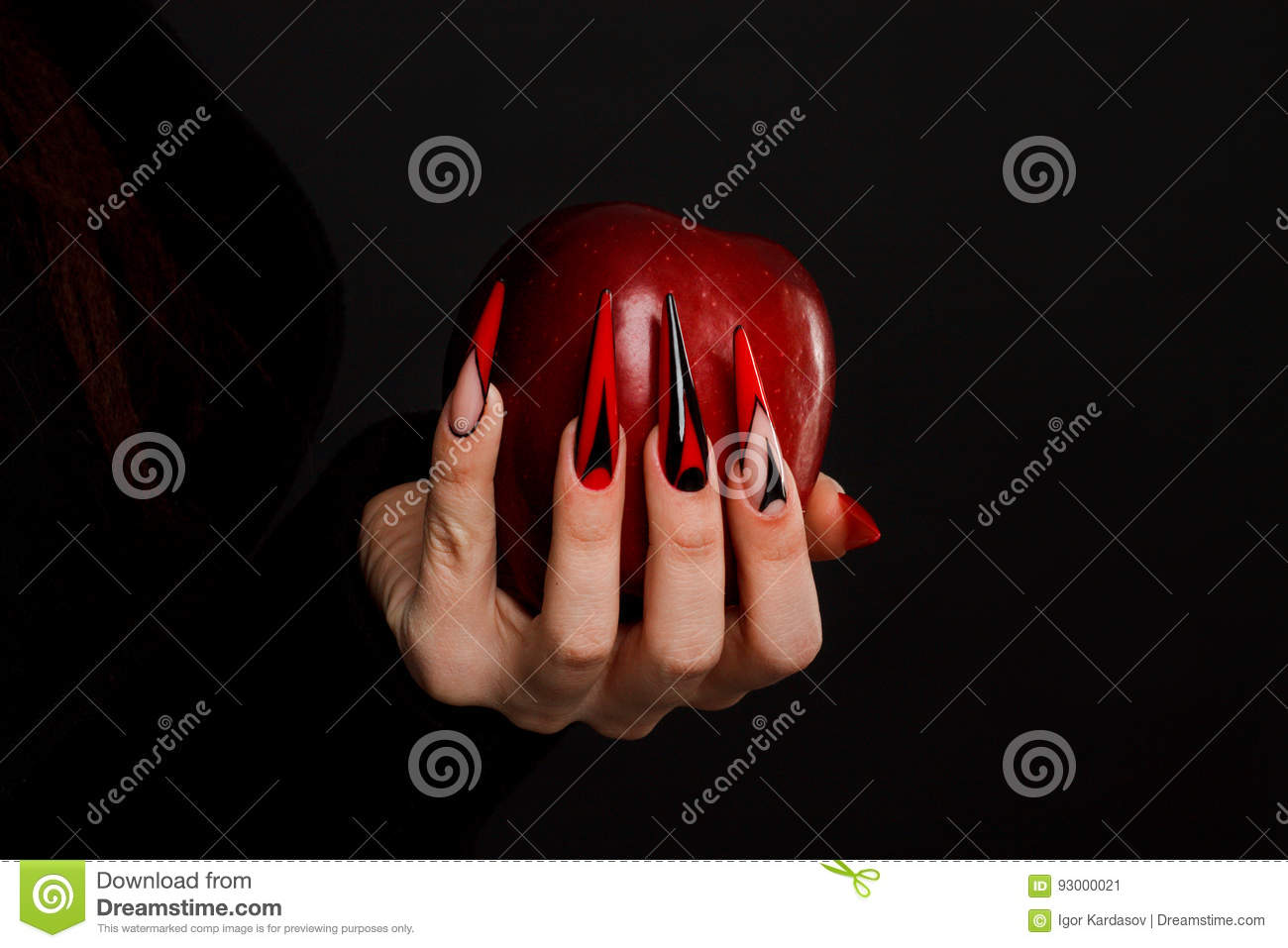 Hands with scary nails manicure holding poisoned red apple