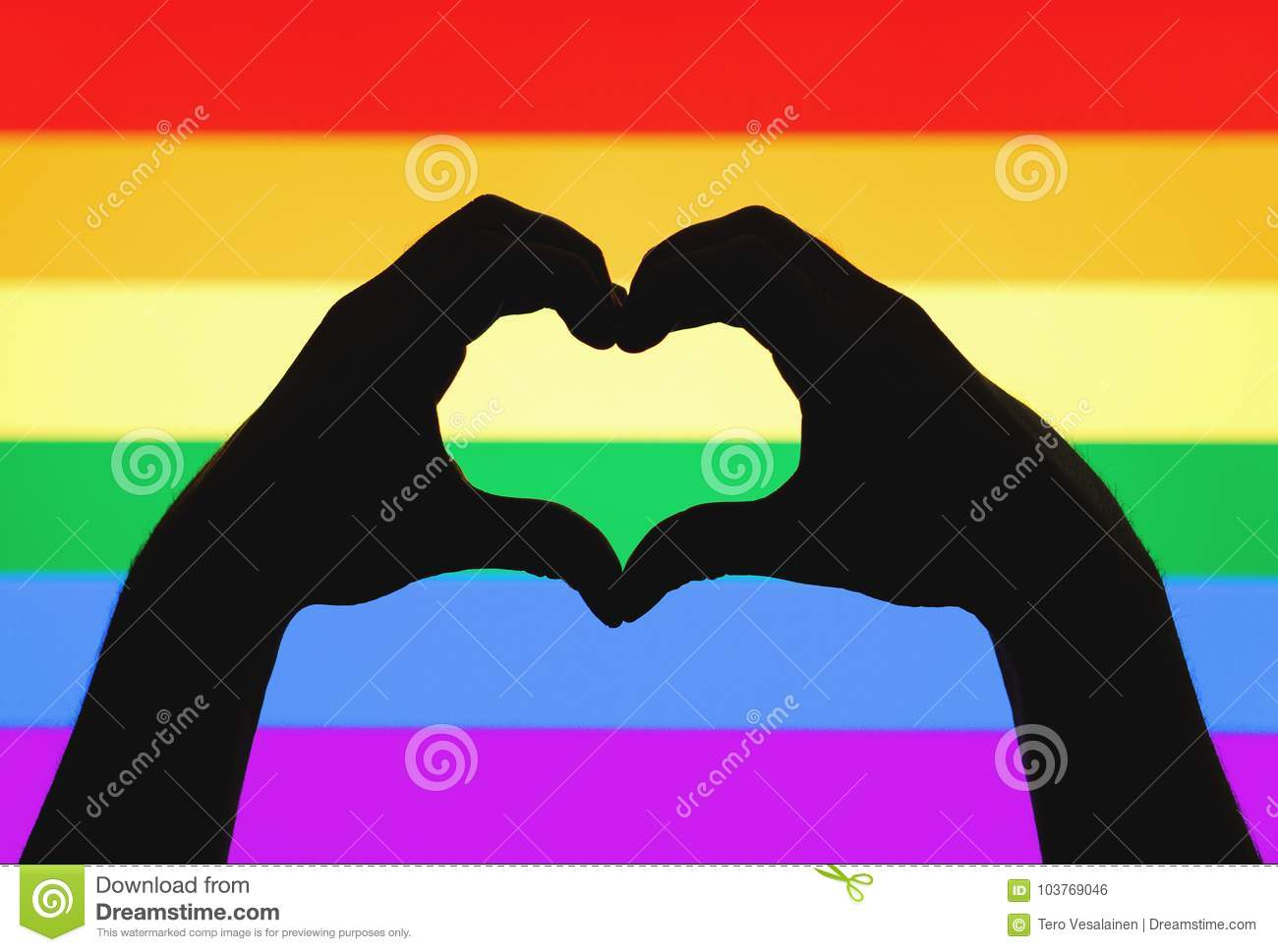 Hands showing heart sign on gay pride and LGBT rainbow flag