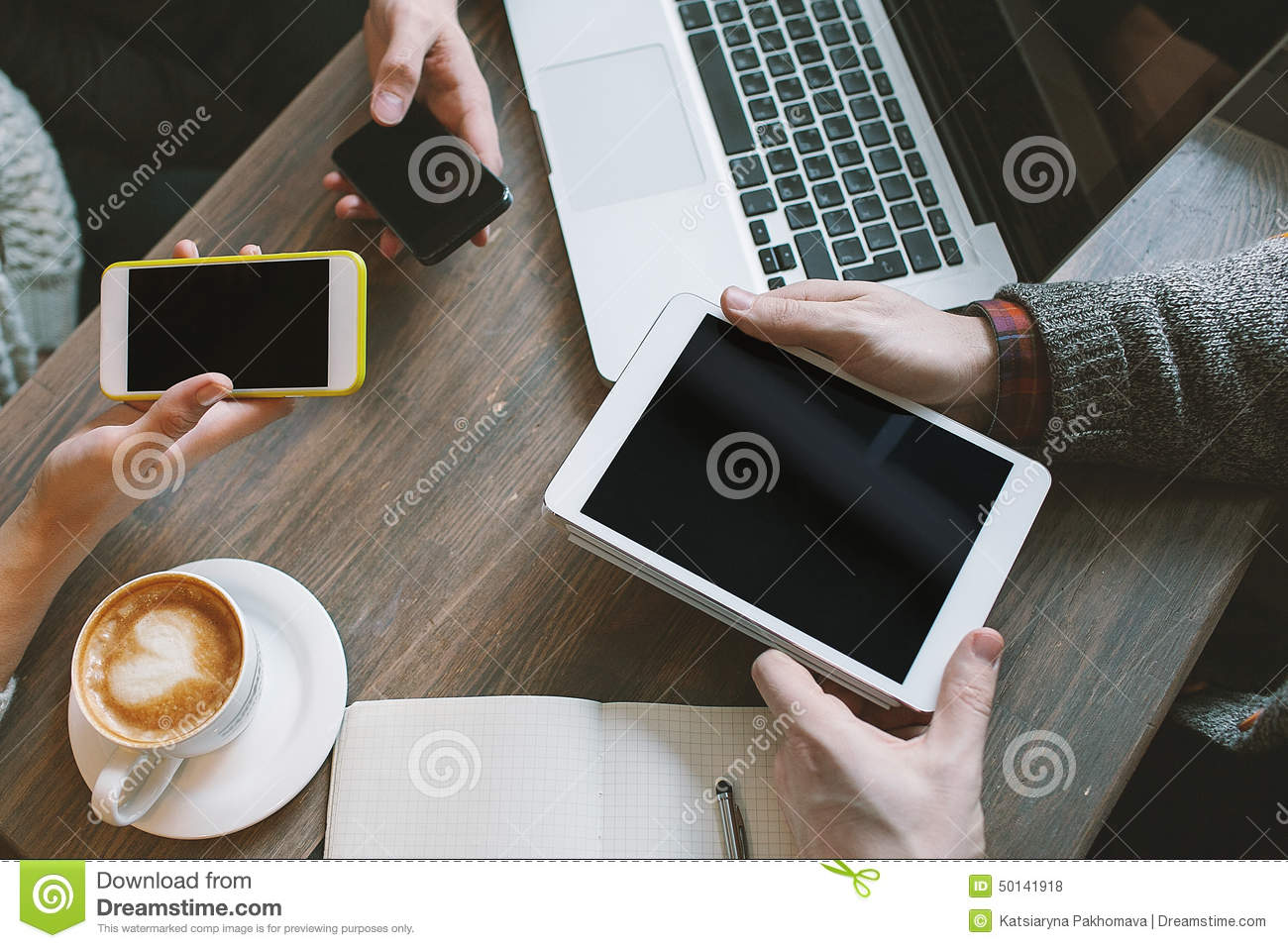 hands with smartphones, tablet over table with laptop and coffee
