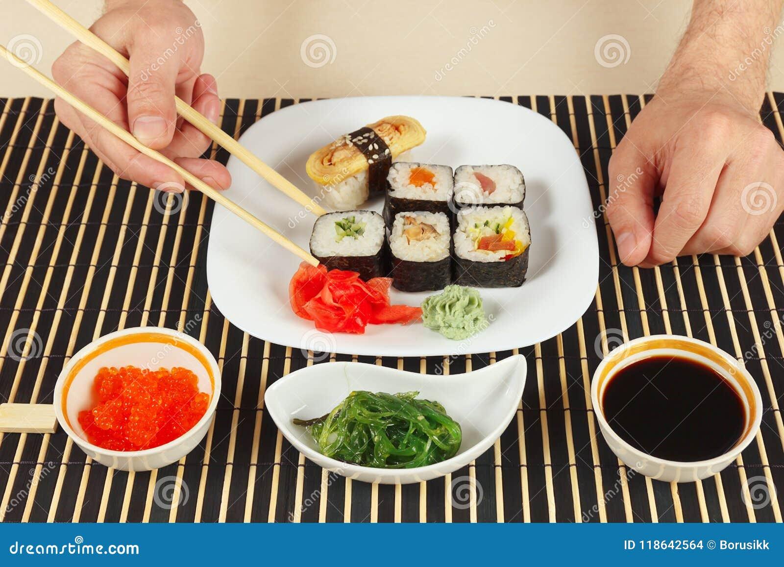 Hands Taking Sushi With Chopsticks Sushi Set Chuka Salad