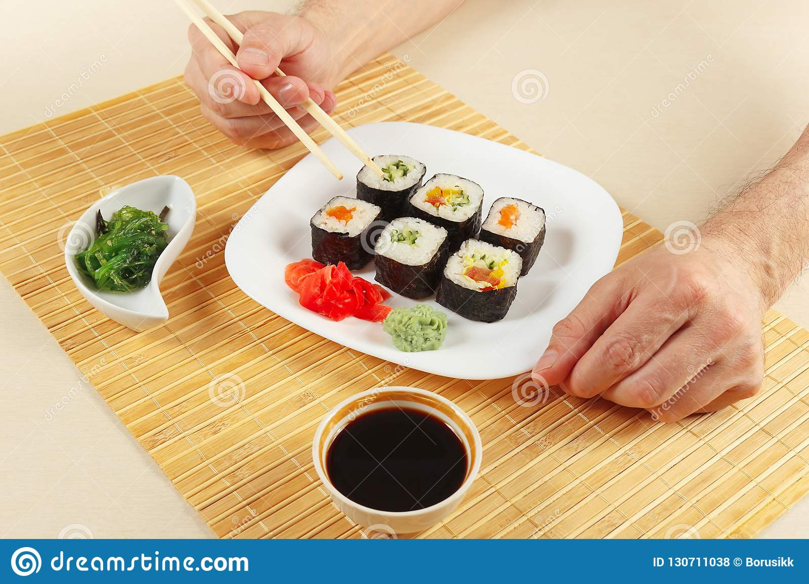 Hands Taking Sushi With Chopsticks Sushi Set With Ginger