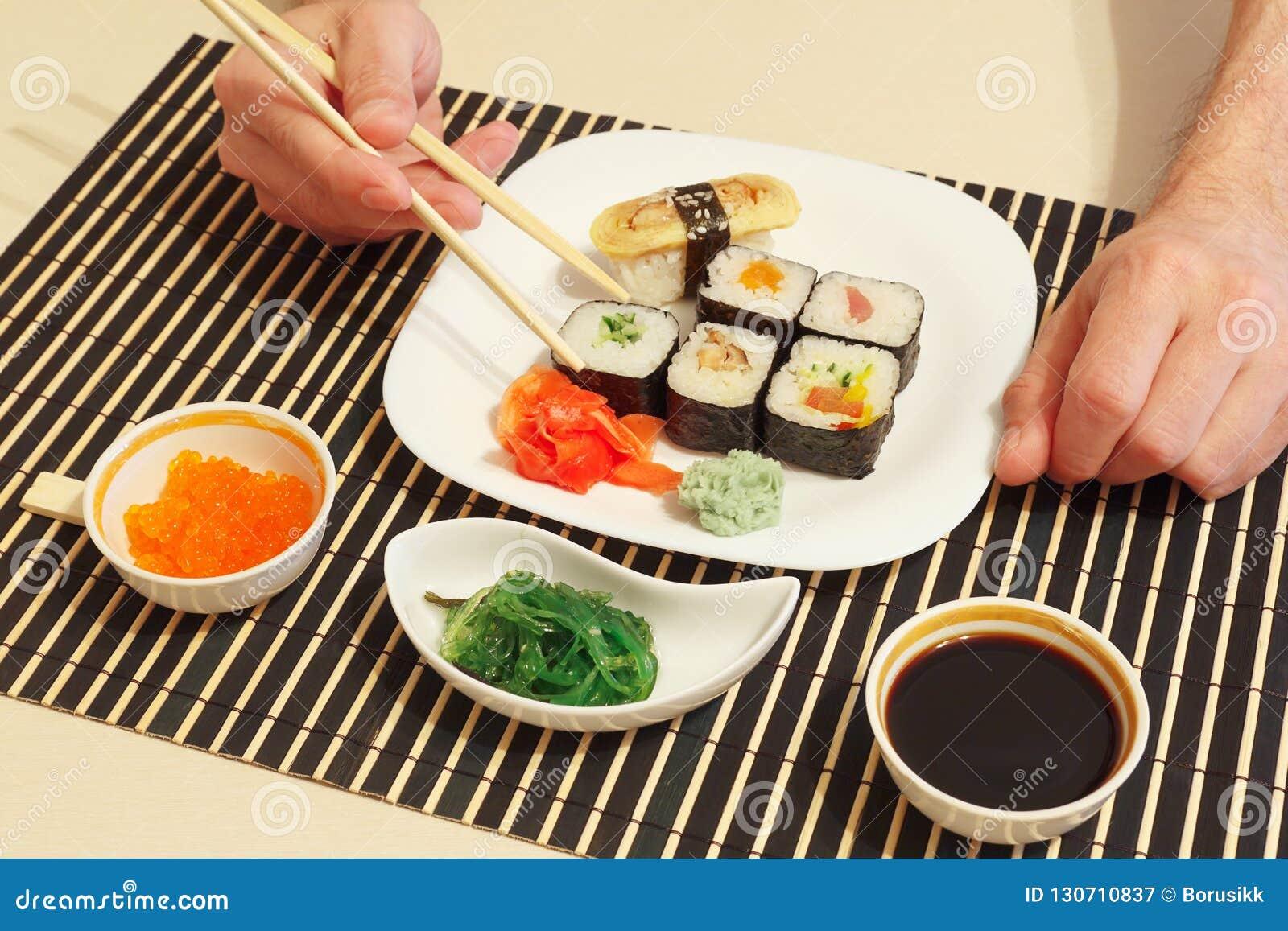 Hands Taking Sushi With Chopsticks Sushi Set Hiyashi