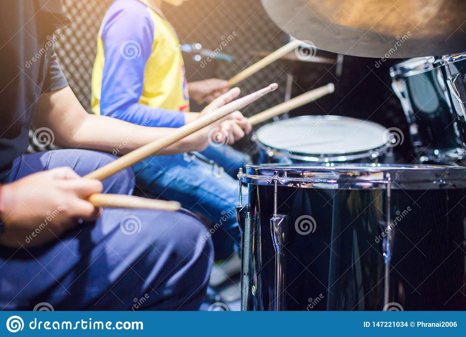 Hands Of Teacher With Wooden Drumsticks Guiding Boy In Drum Learning