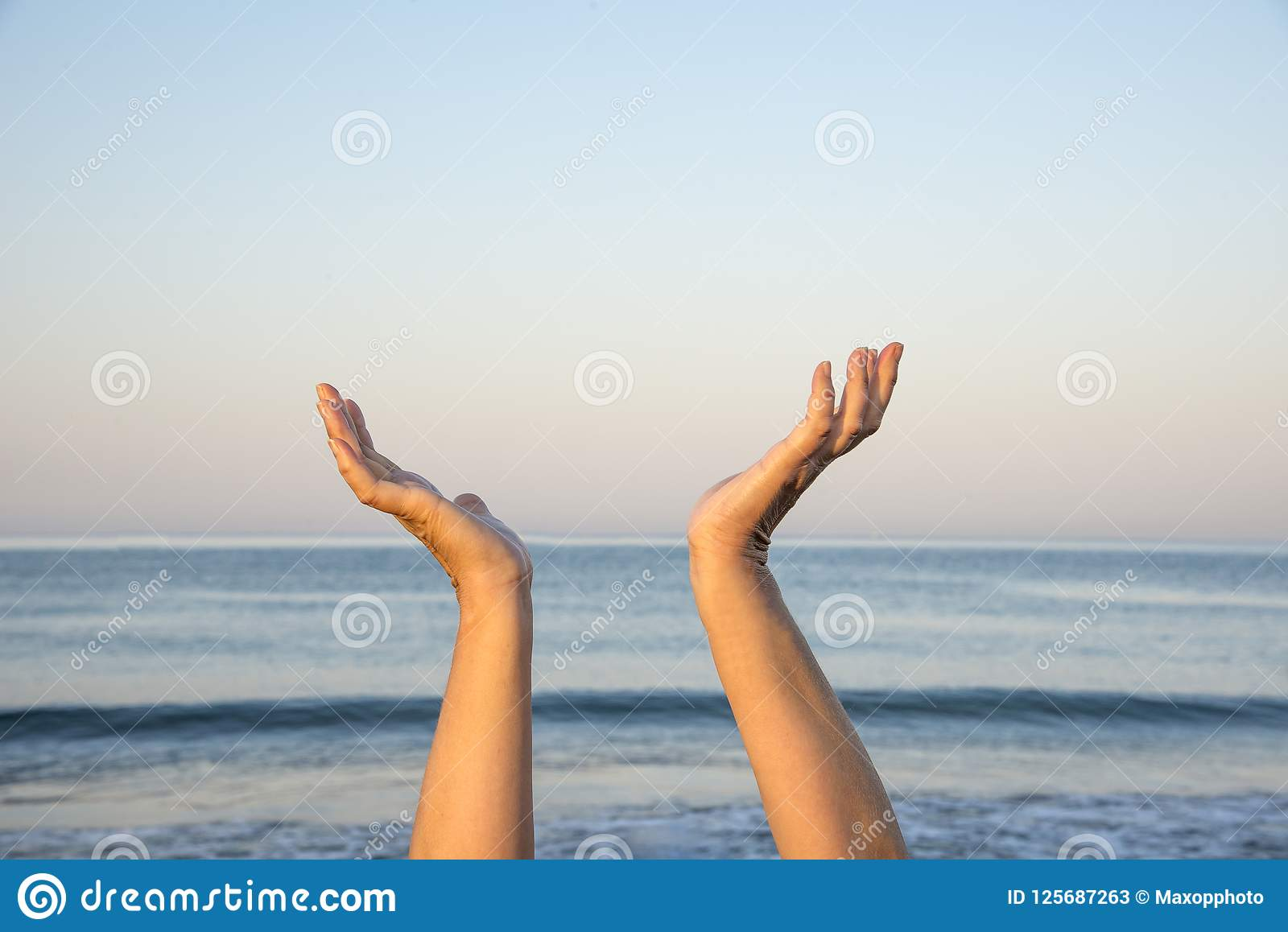Hands up in the air by the sea. The hope and spiritual concept.