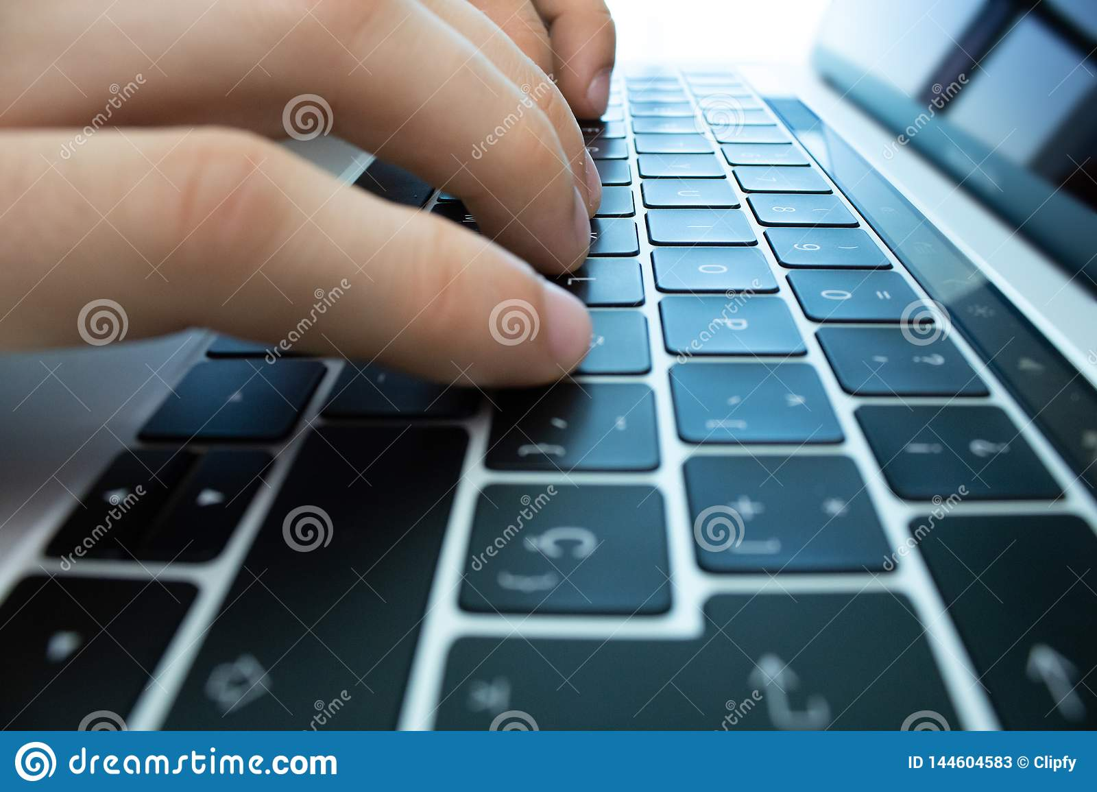 Hands using the keyboard and touchpad of a laptop computer on a white table