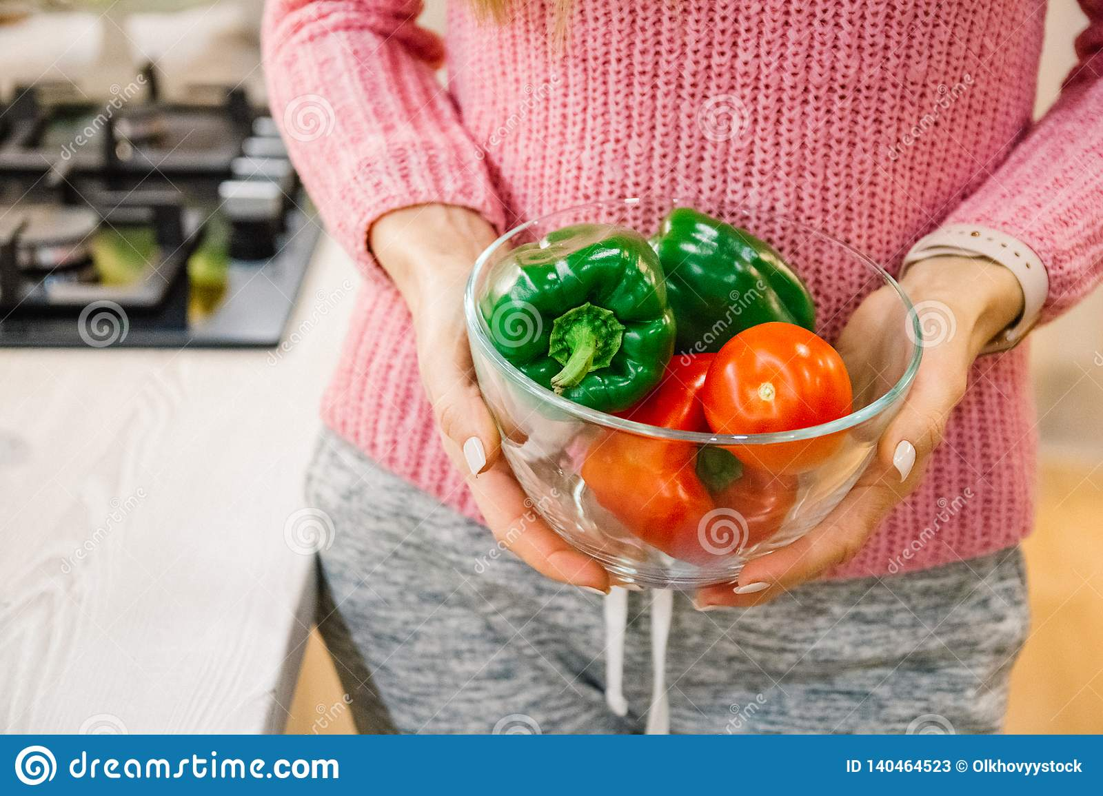Hands washing fresh vegetables paprika red, green, yellow, in glass bowl
