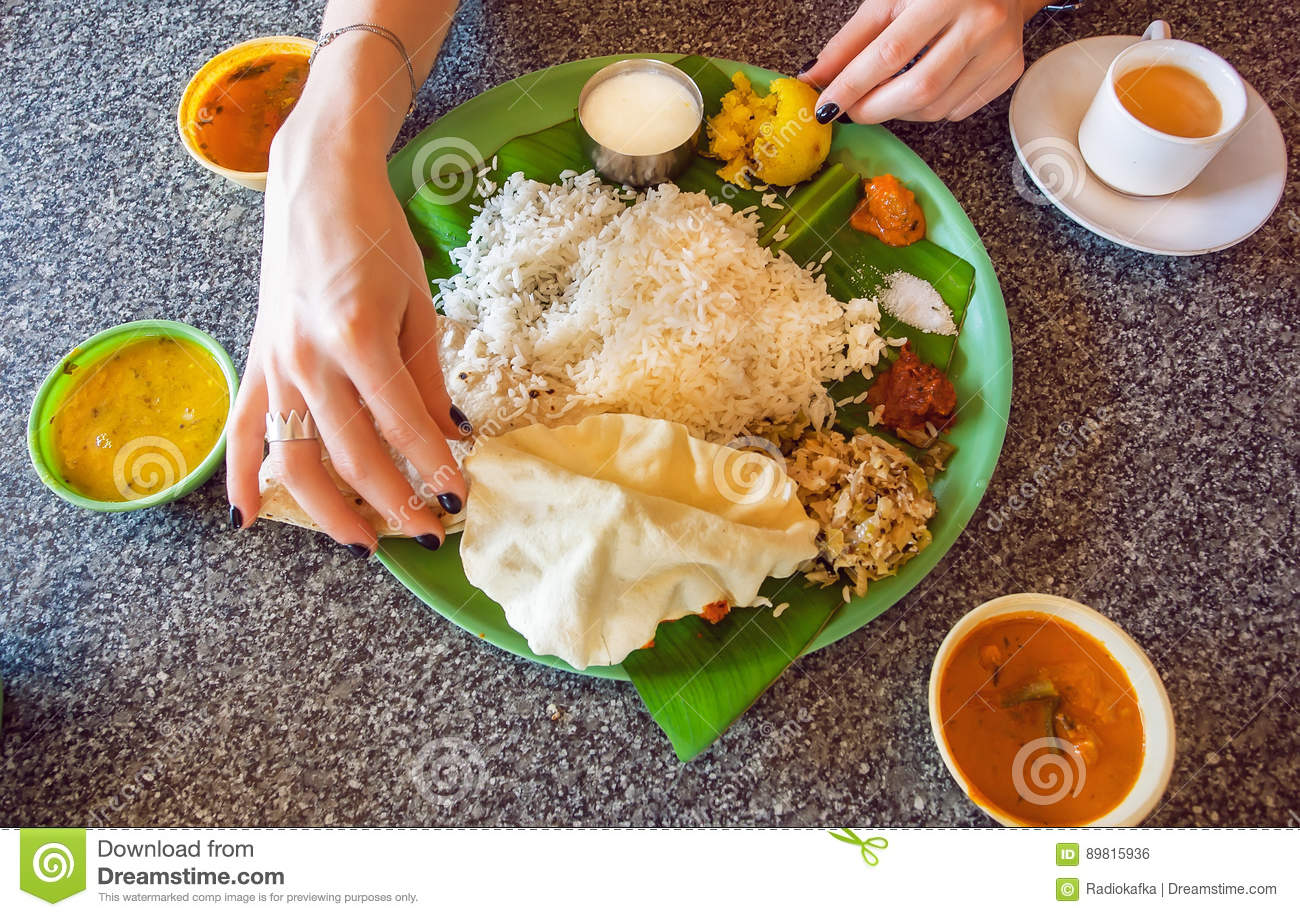 Hands of woman on table with traditional south indian food for Authentic south indian cuisine