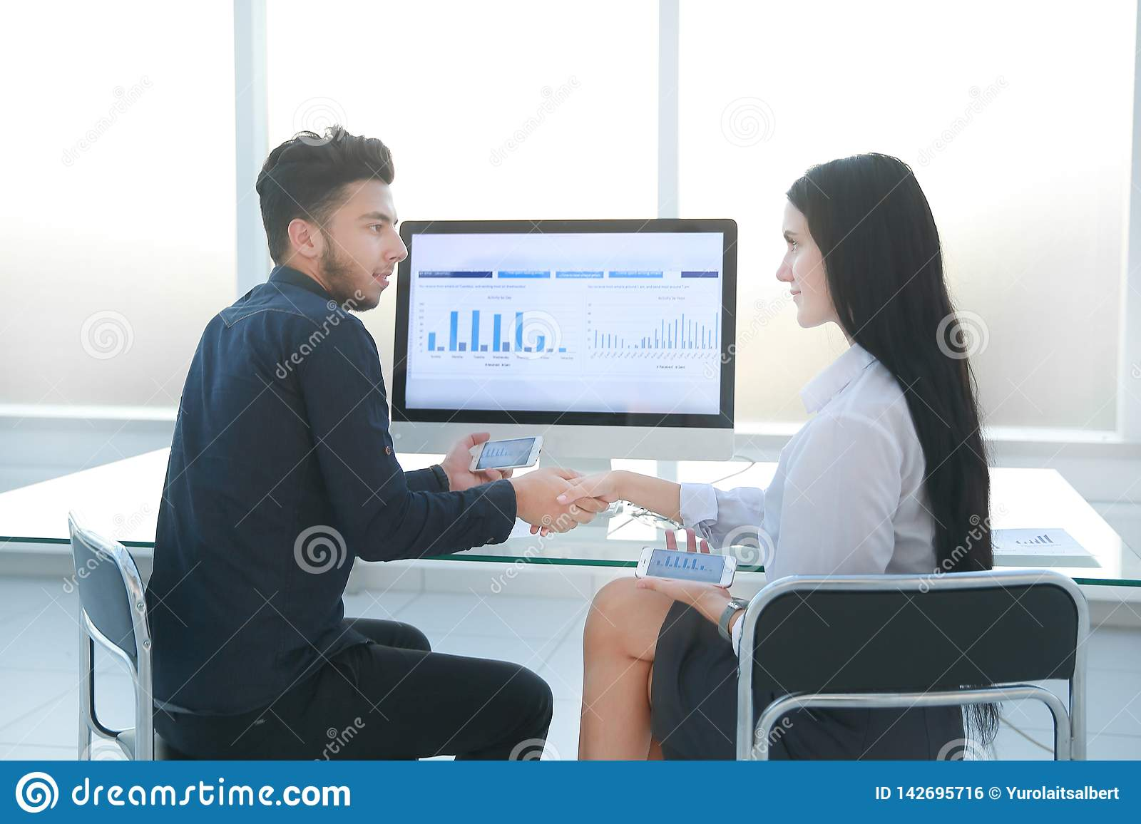 Handshake of a businessman and businesswoman near office Desk.