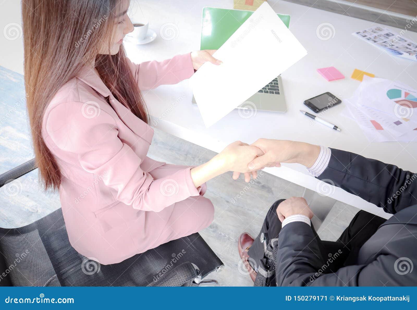 Handshaking między młodym biznesowym mężczyzną i kobietami popełnia biznesowego partnerstwo kontrakt