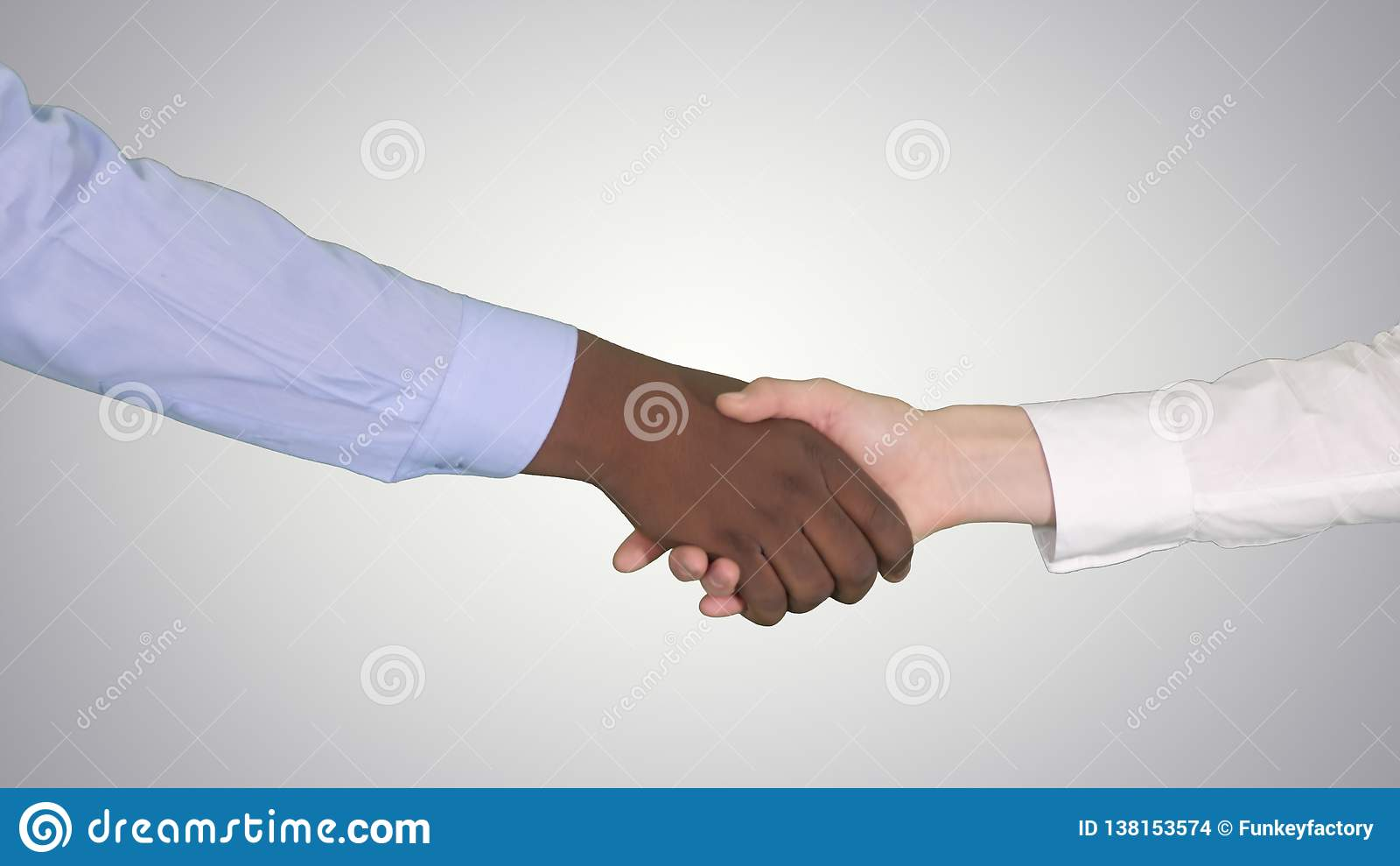 Handskakning av afro- amerikanska och caucasian kvinnliga händer på lutningbakgrund