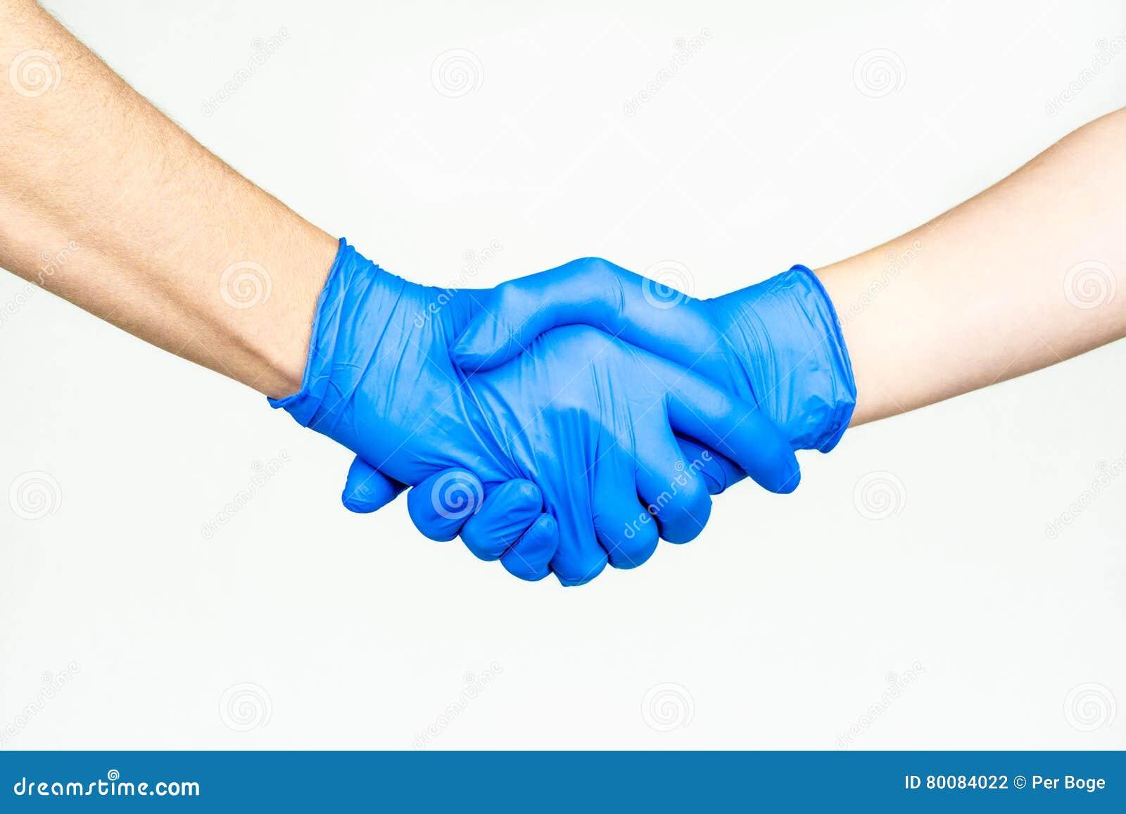 Handskakning med blåa medicinska handskar