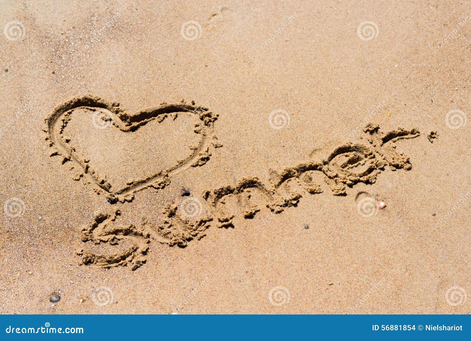 Handskriven sommar i sanden av stranden med en älskvärd hjärta
