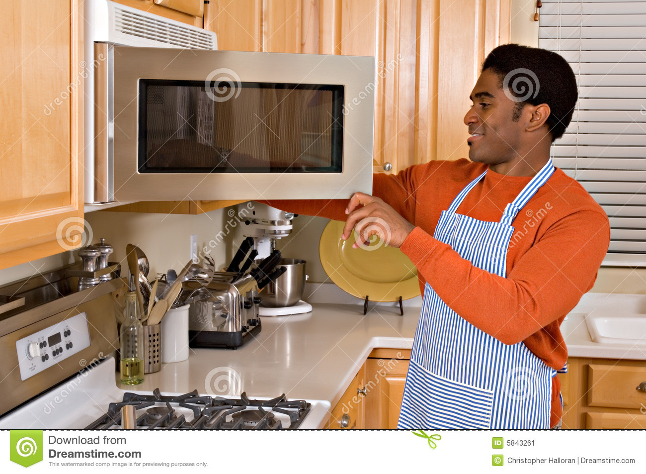 Handsome african american man cooks in kitchen stock image for African kitchen