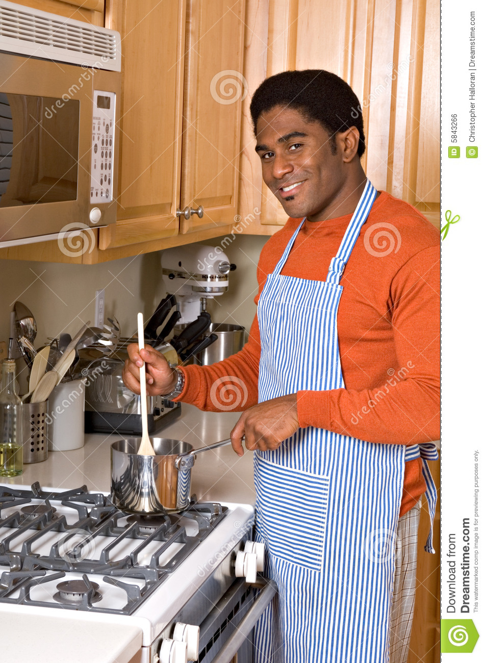 Handsome African-American man cooks in kitchen
