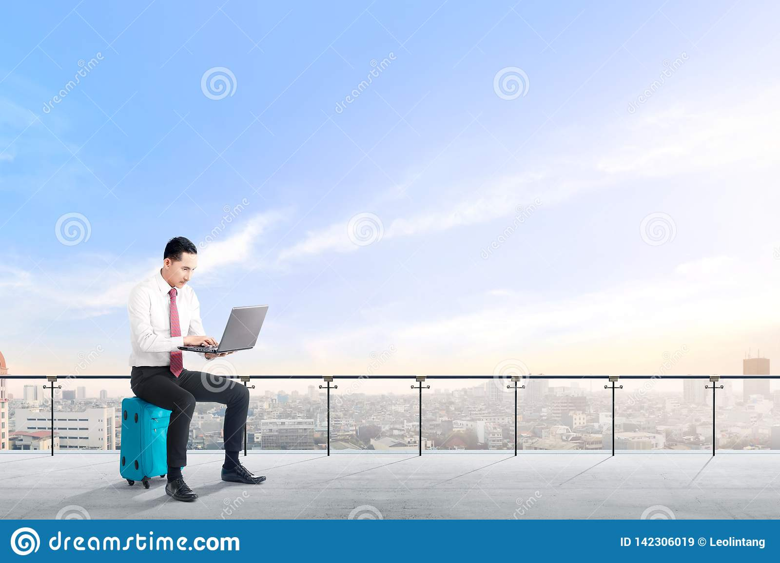 Handsome asian businessman sitting on blue suitcase hold the laptop and working on modern terrace