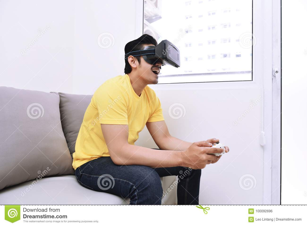Handsome asian man wearing virtual reality while playing video g