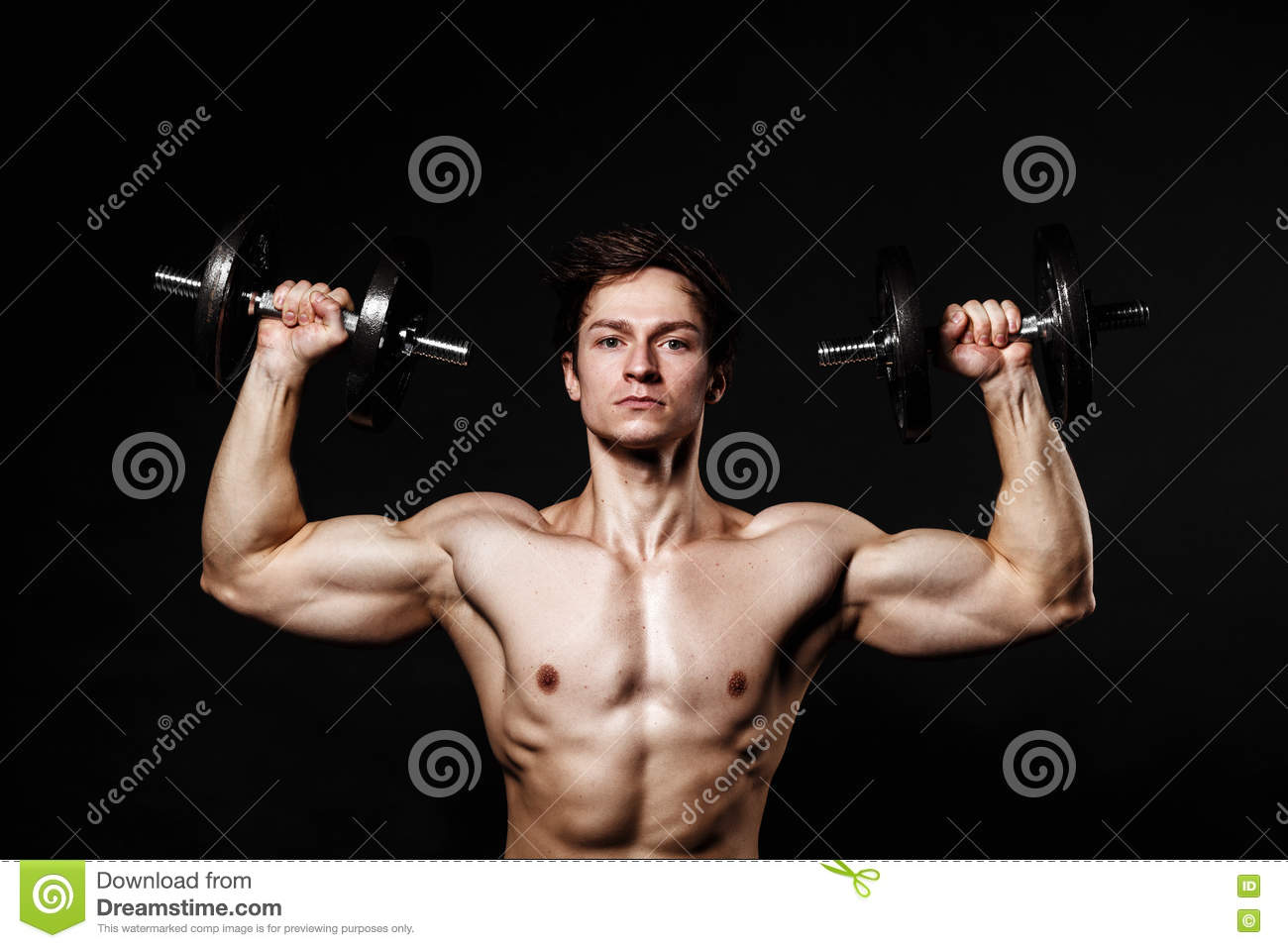 Handsome athletic man with dumbbells confidently looking forward