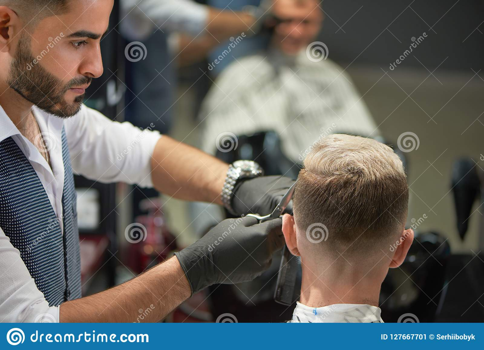 Handsome barber in black gloves cutting haircut of man using scissors.