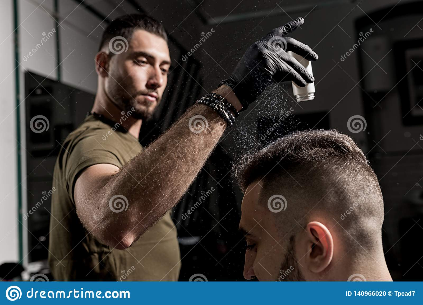 Handsome barber is fixing the styling of brutal young bearded man with a dry styler at a barbershop