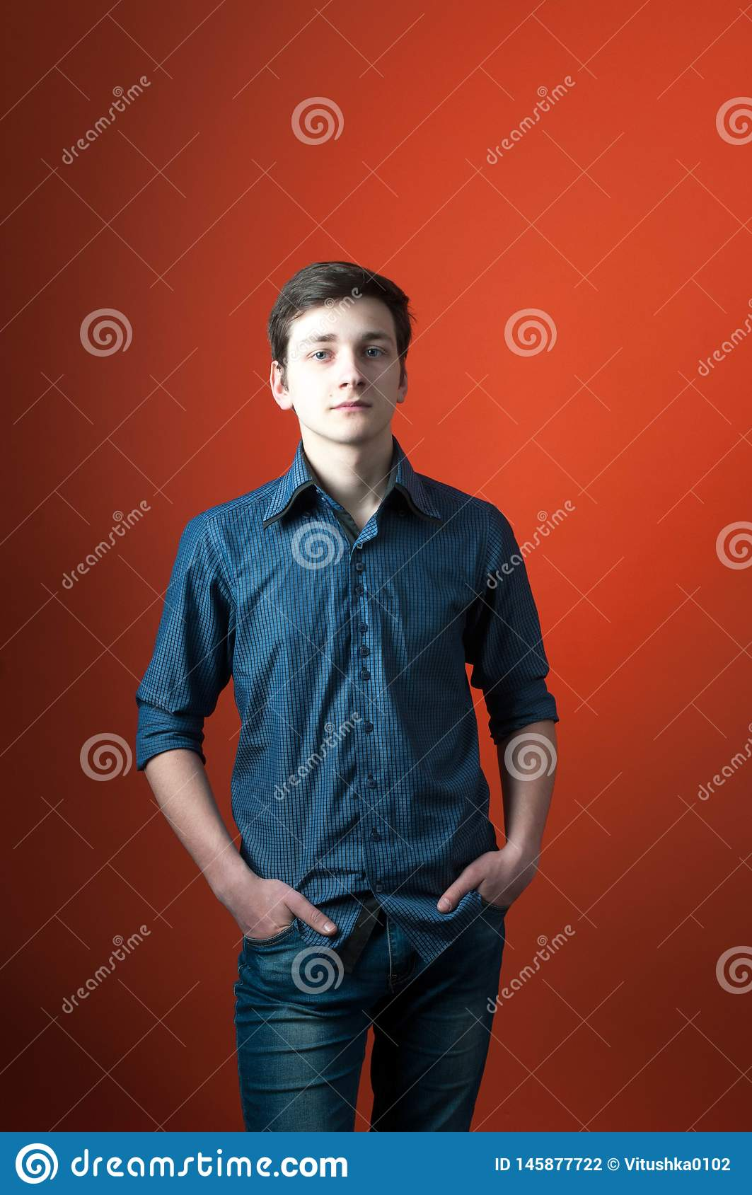 Barista in blue shirt and jeans standing with hands in pockets and looking at camera on orange background