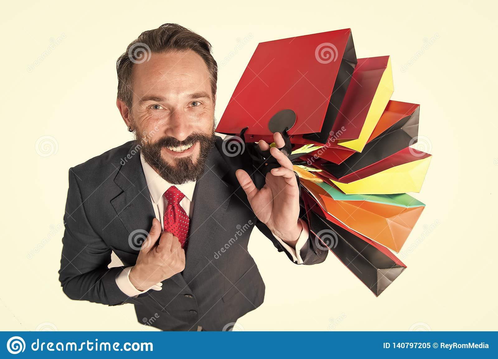 handsome beaded man with lot of shopping bags top view. man in suit happy from shopping time and presents for friends. Sales and