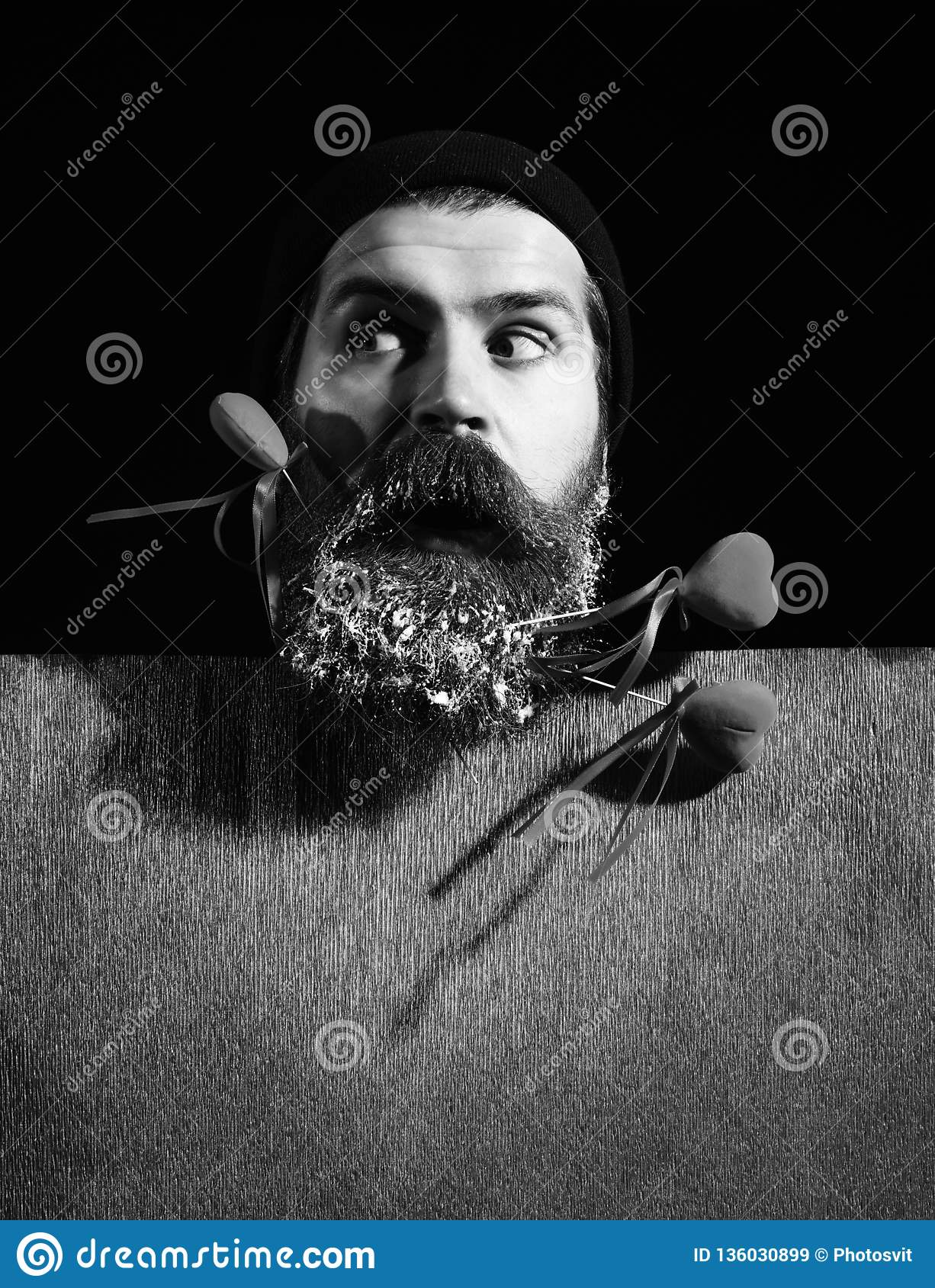 103e4f55977 Handsome bearded man or guy in winter hat with fashionable mustache on  surprised face and snow in beard with decorative valentines hearts on  sticks near red ...
