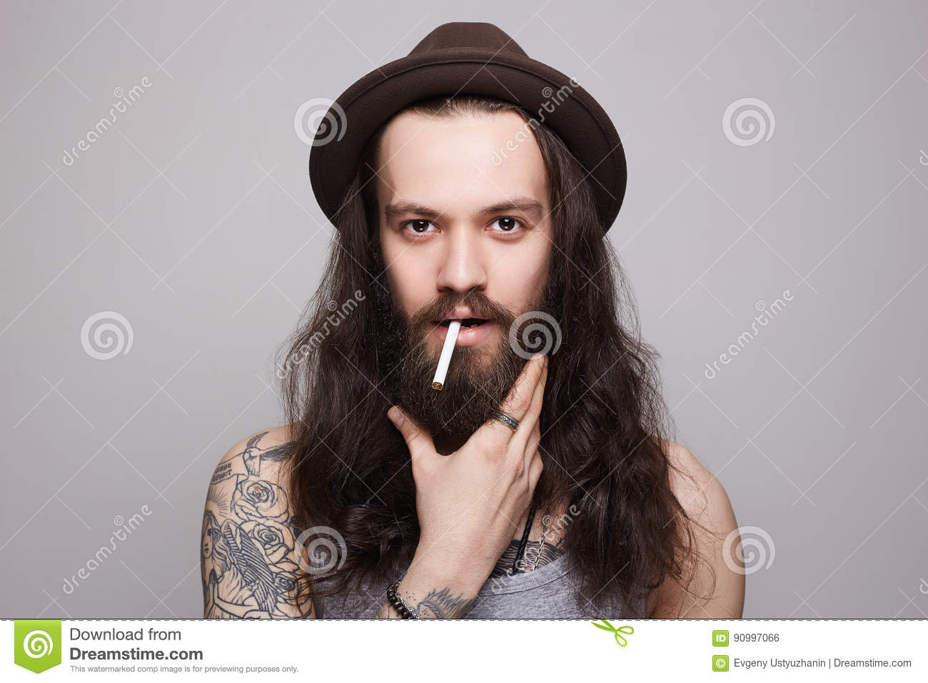 Handsome Bearded Man In The Hat Smoking A Cigarette Stock