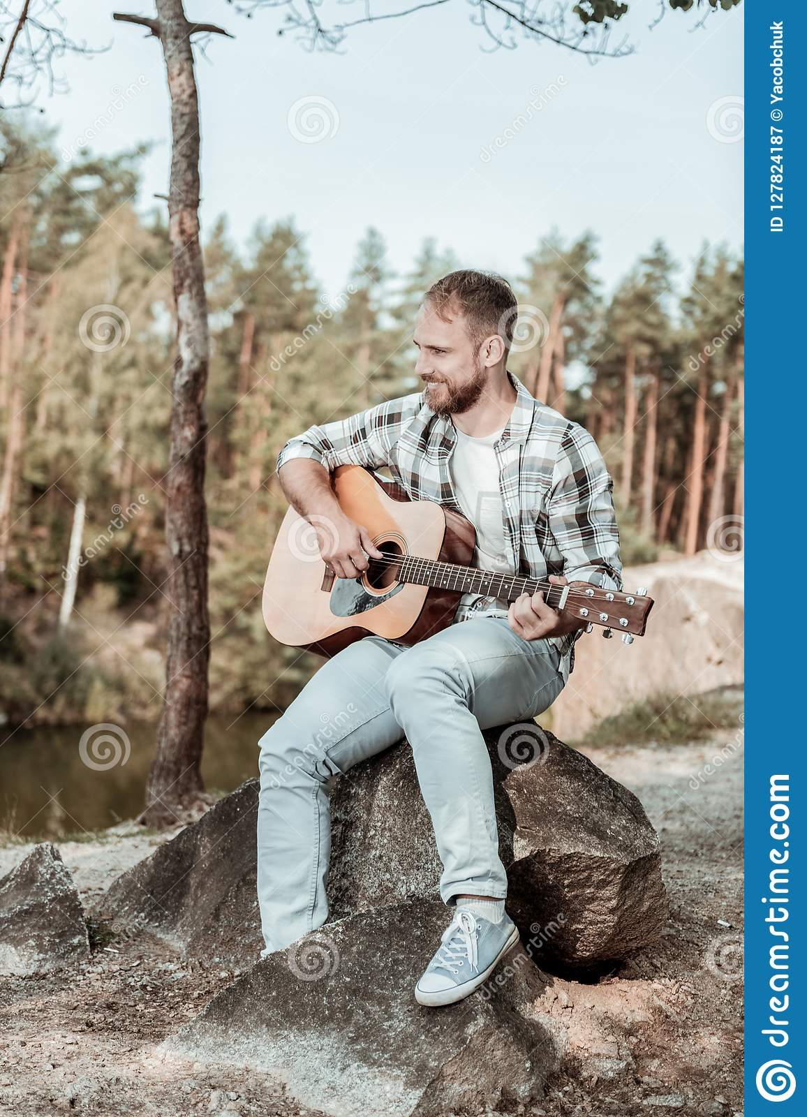 Handsome bearded man wearing jeans and squared shirt playing the guitar near lake