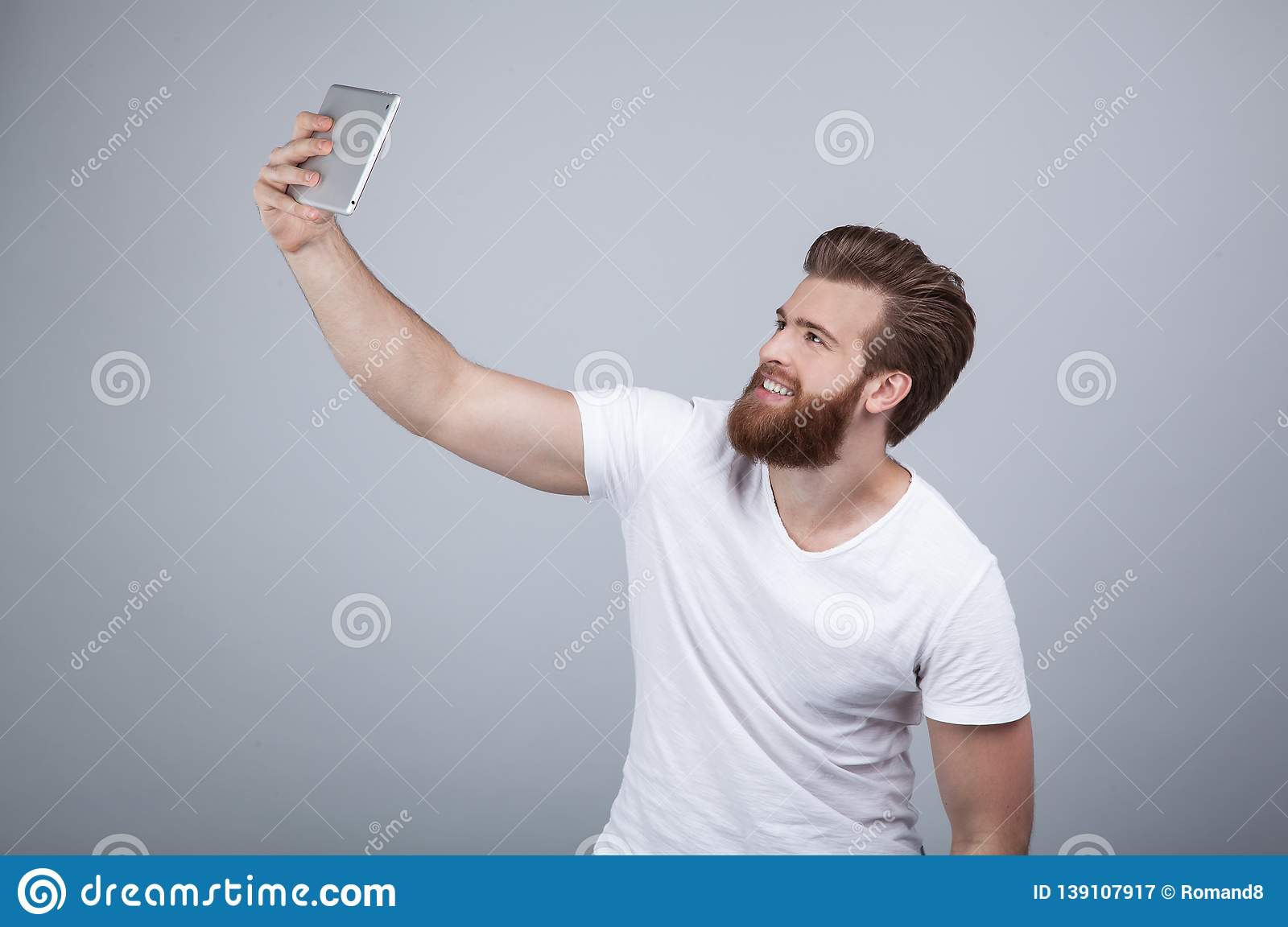 Handsome bearded young man is making selfie and smiling. He is in white t shirt