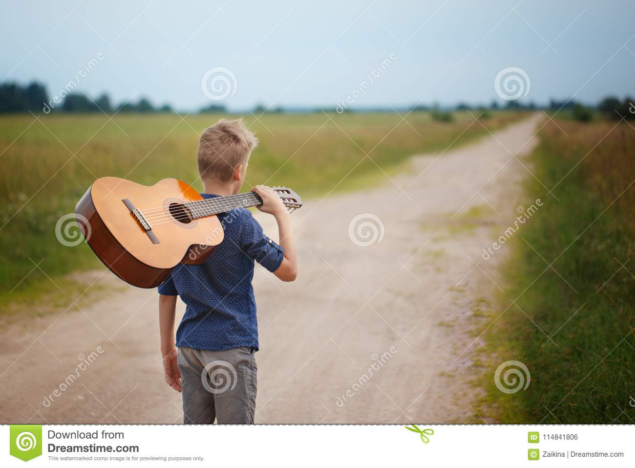 521b1d396 Handsome boy with guitar walking on the road in summer day. Back view