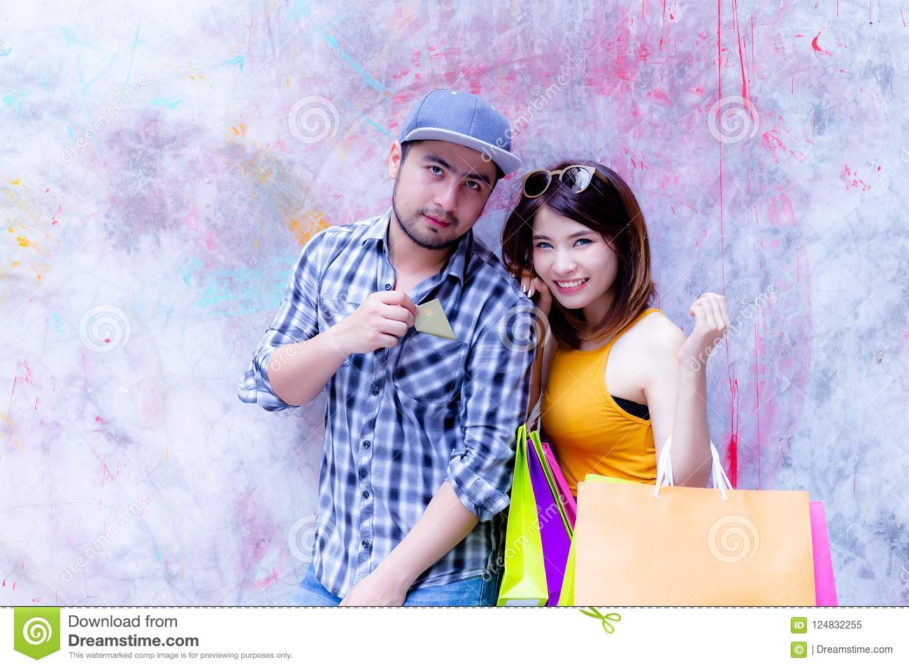 Handsome boyfriend is taking girlfriend to shopping mall. Handsome guy use credit card for buying favorite goods. Beautiful
