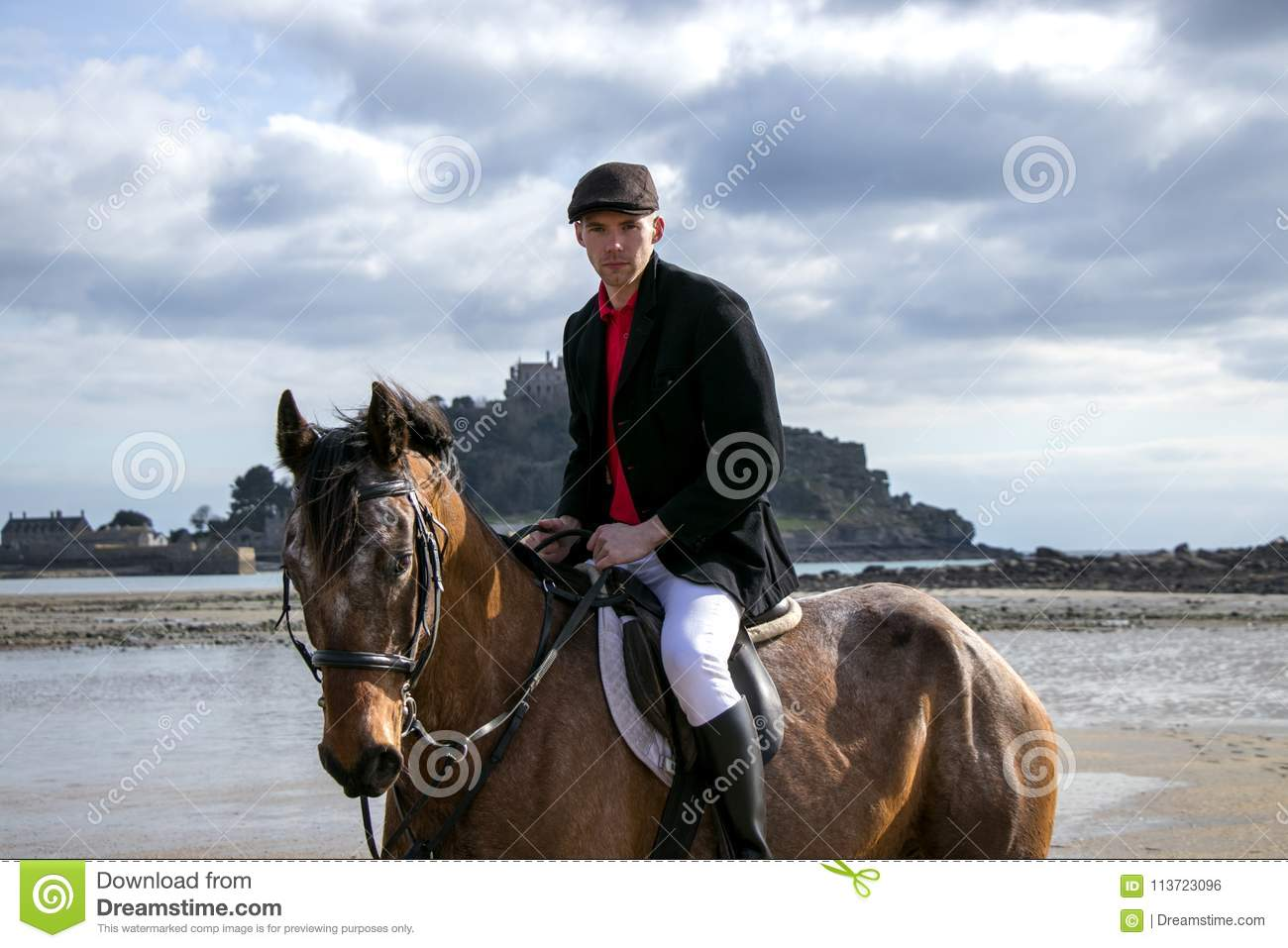 Good Looking Male Horse Rider Riding Horse On Beach In Traditional Riding Clothing With St Michael S Mount In Background Stock Photo Image Of Beautiful Equine 113723096