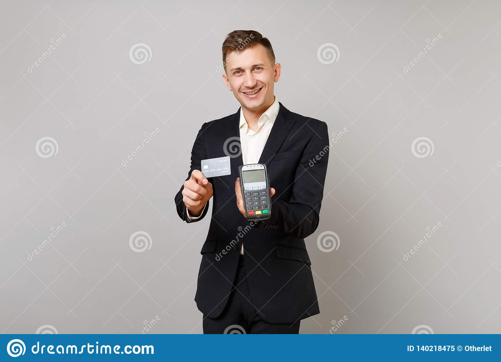 Handsome business man holding wireless modern bank payment terminal to process and acquire credit card payments black