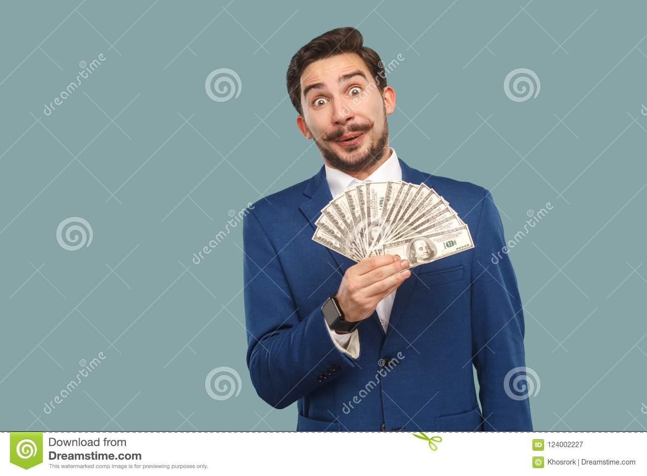 Handsome businessman in blue jacket standing and holding many do