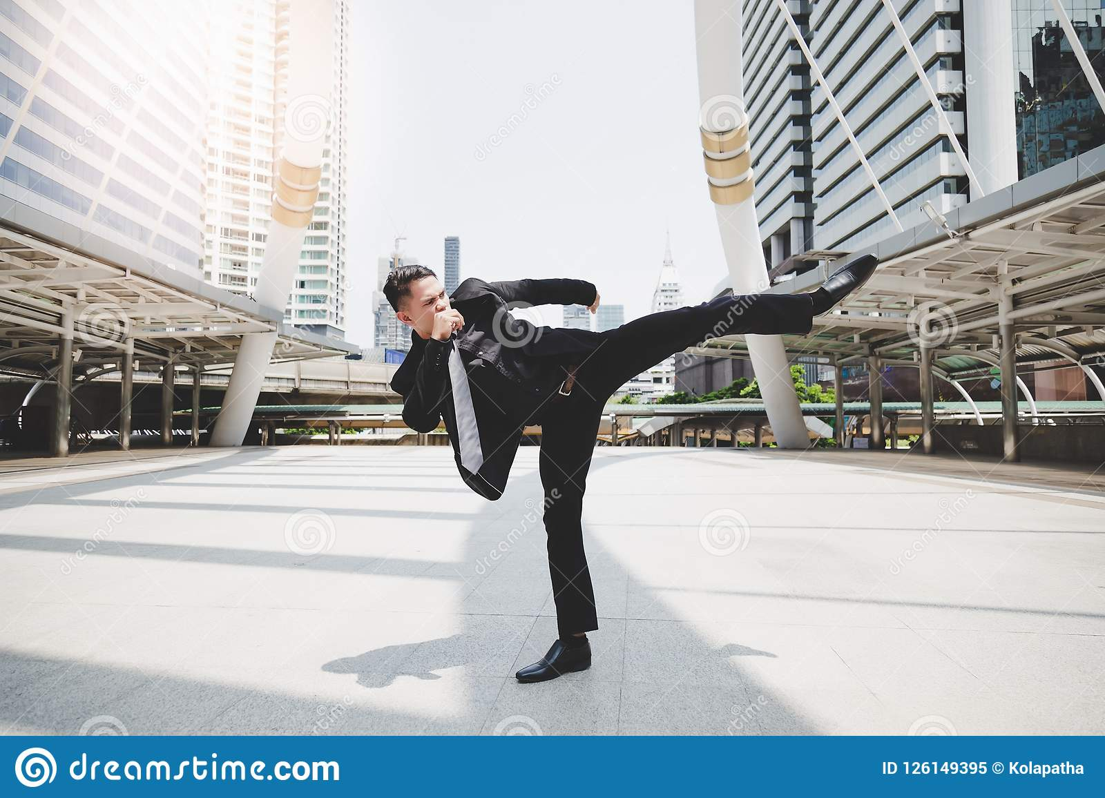 Handsome businessman get angry his boss and wants to relieve stress and furious. Cool guy is exercising by kicking on the air. At