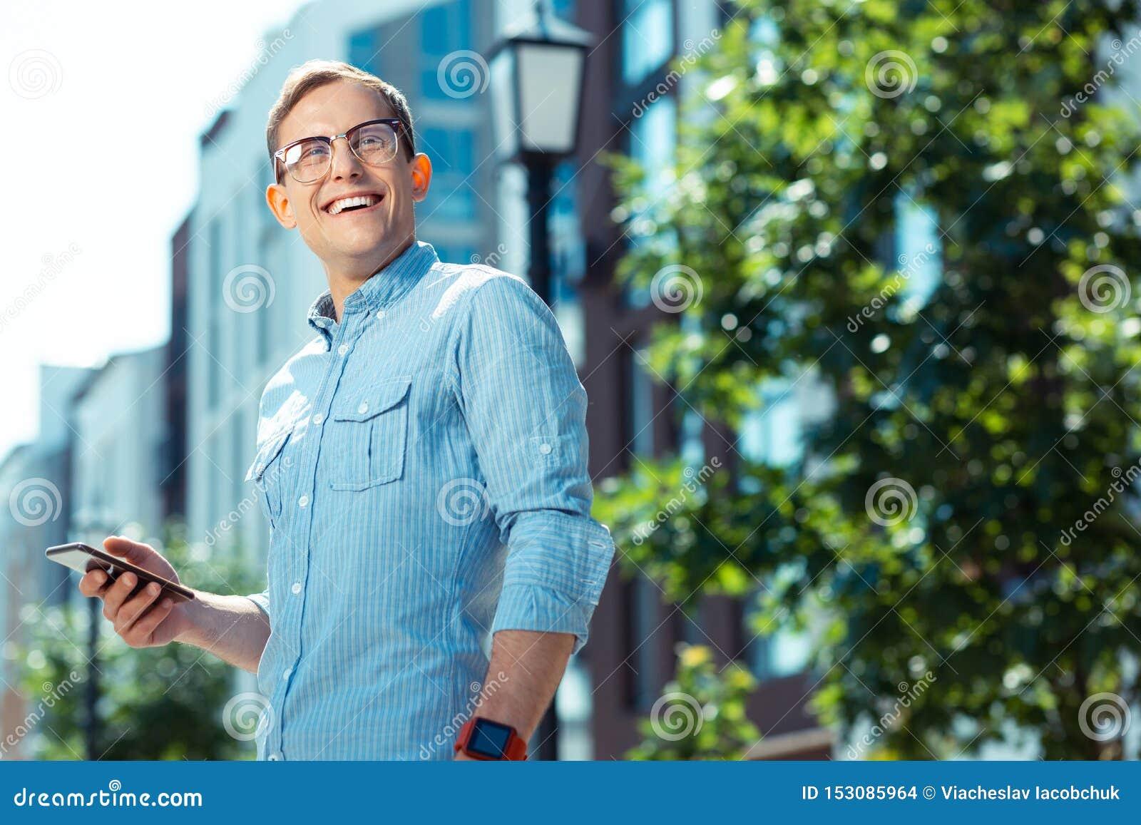 Handsome businessman smiling broadly while enjoying weekend walk