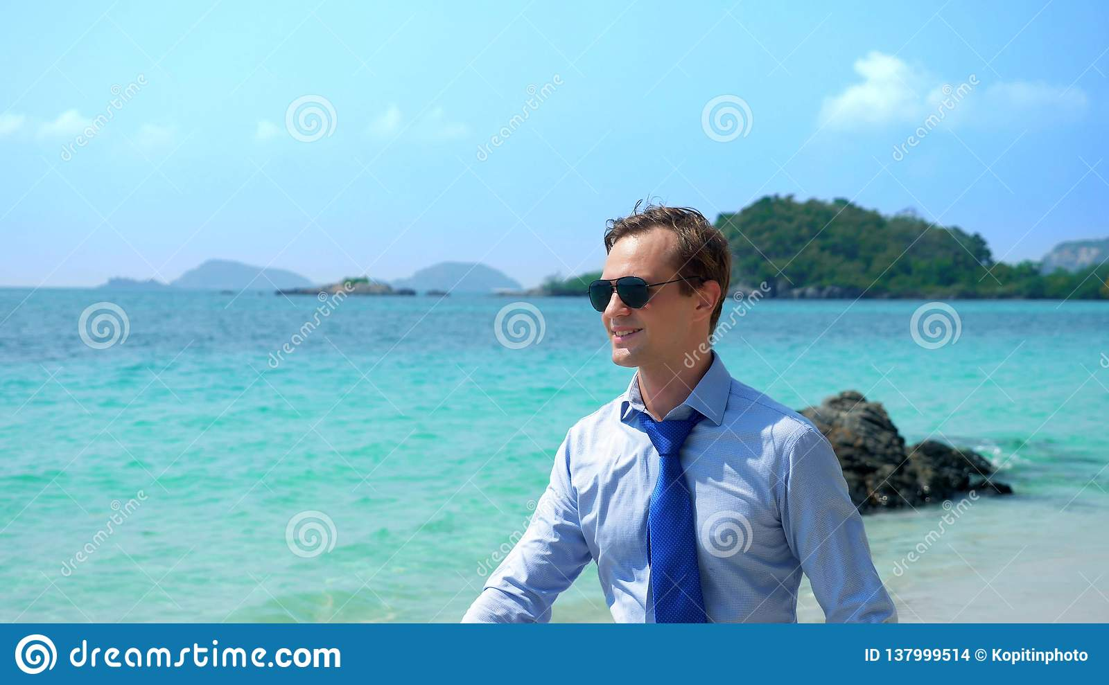 Handsome businessman in sunglasses walked along a tropical beach, taking off his tie