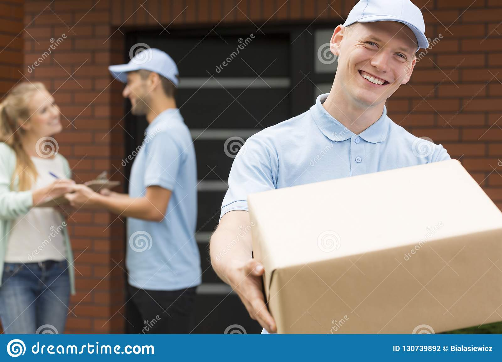Courier in blue uniform holding big brown package and smiling