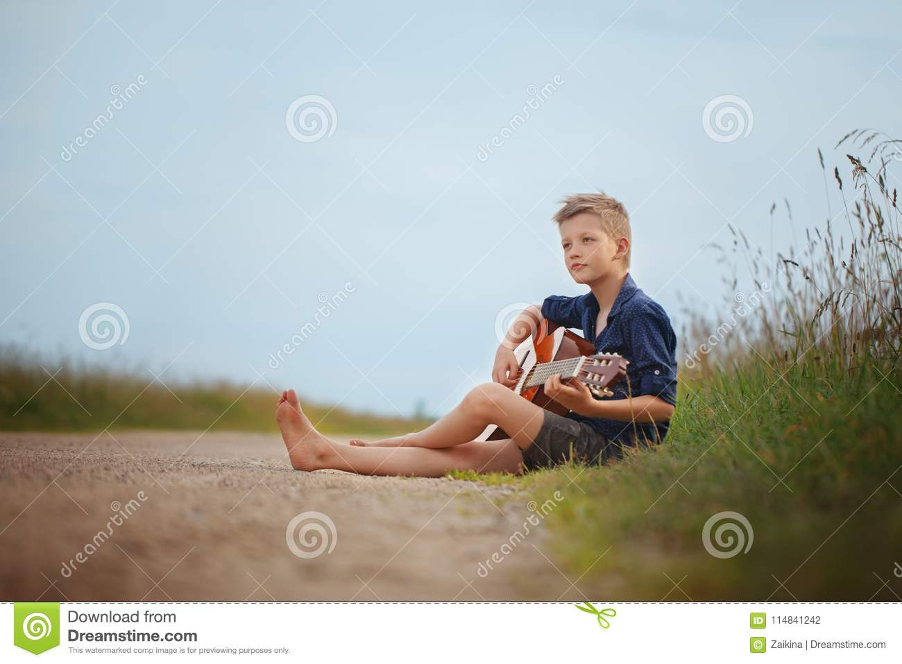 Handsome cute boy is playing on acoustic guitar sittingon road in summer day.