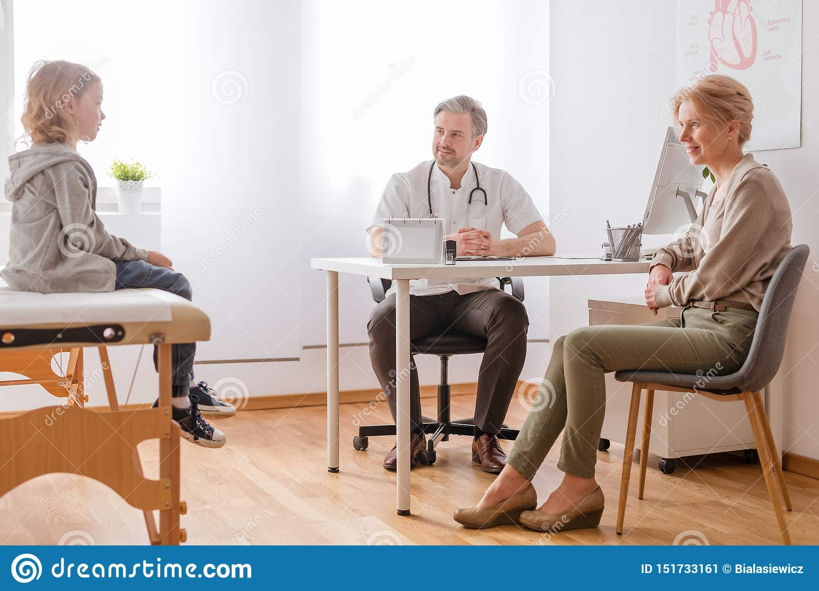 Handsome doctor, mother and son in modern hospital office