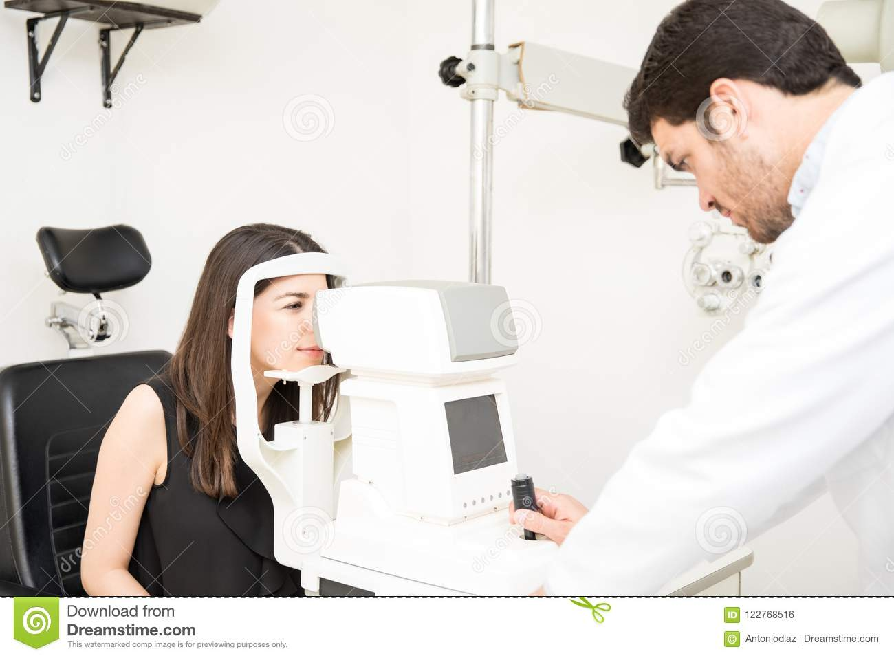 a7cff307e4d Attractive young optician examining women patients eye pressure with  tonometer