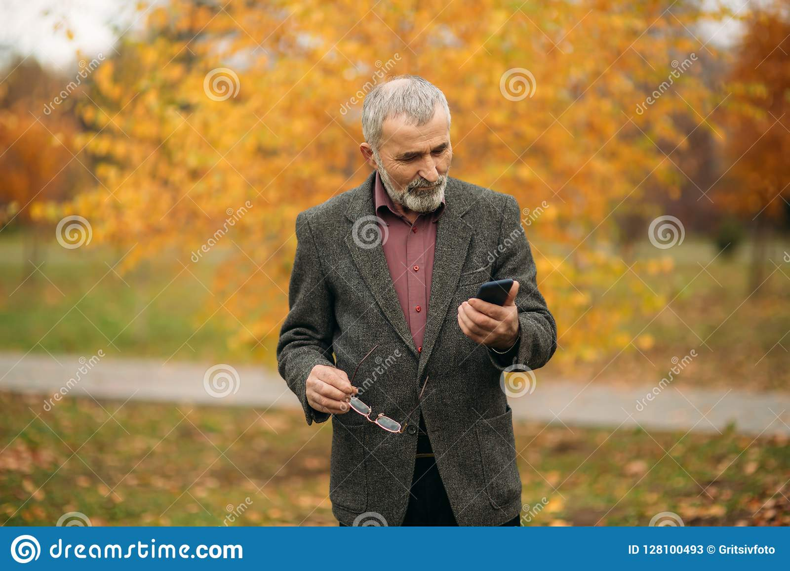 A handsome elderly man with beard in glasses is using a phone. Walk in the park in autumn
