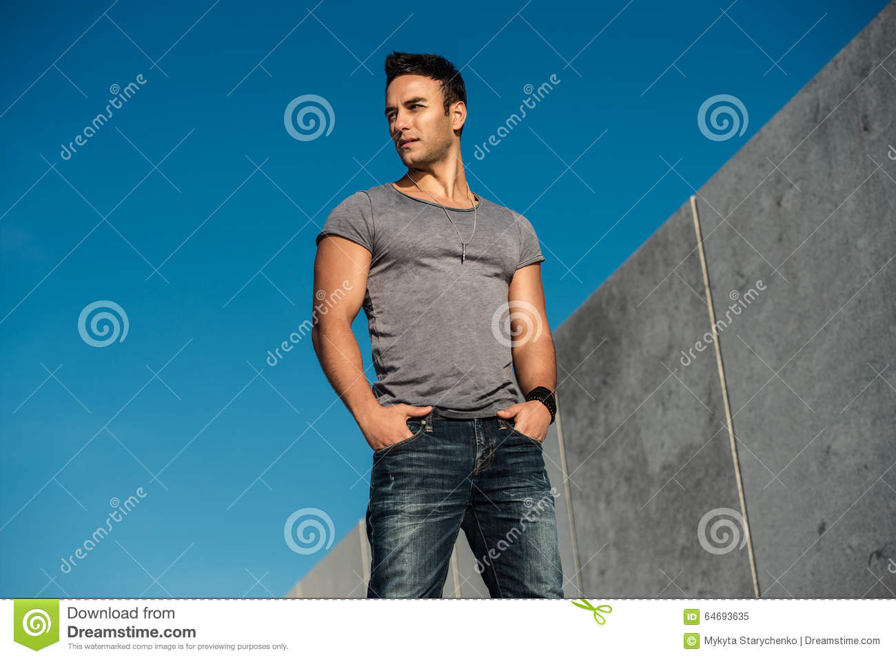 handsome fashion model man posing outdoors wearing grey t
