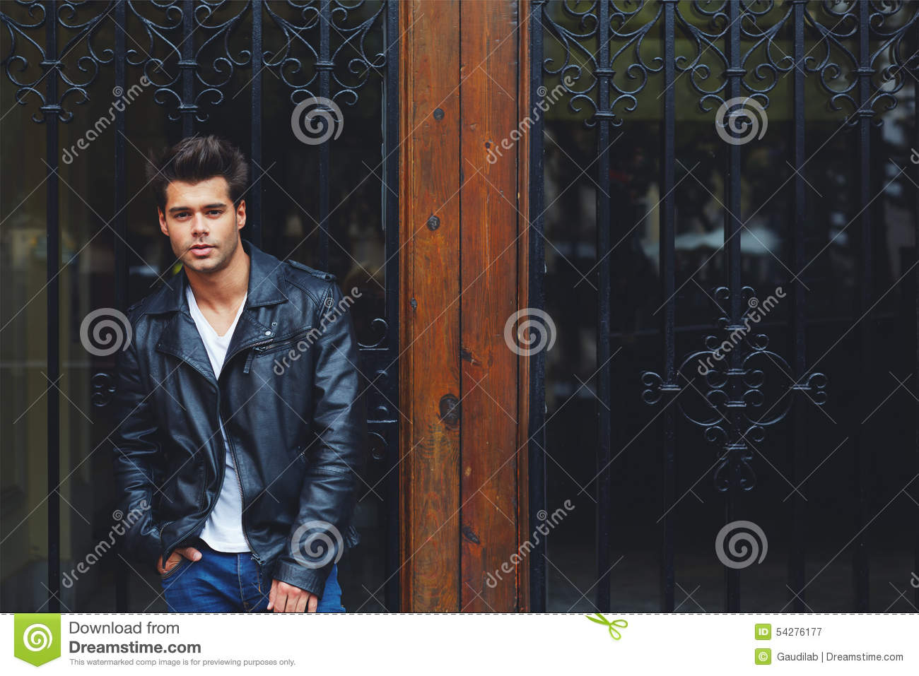 Handsome fashionable male in trendily clothing posing outdoors in the city