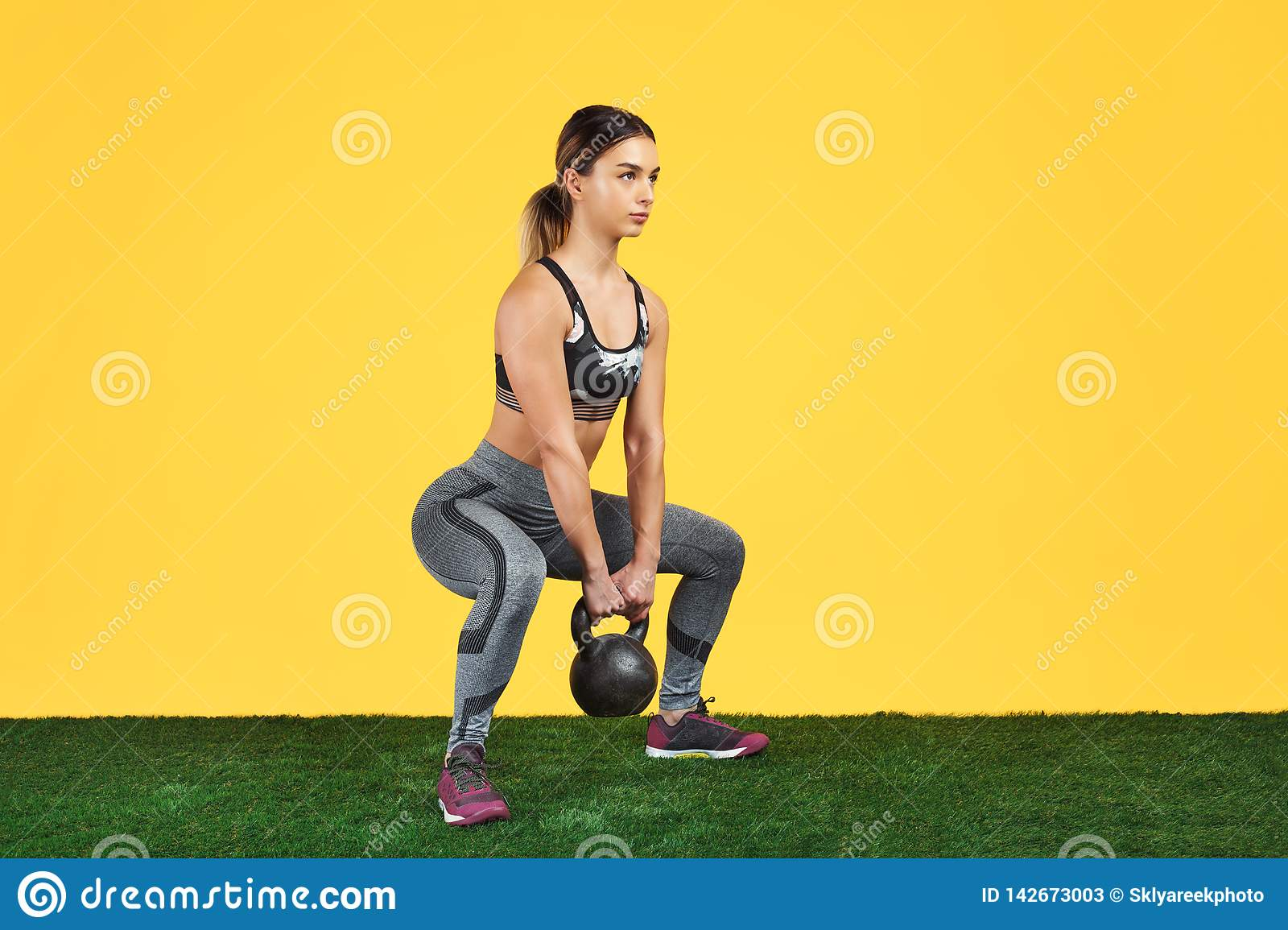 Handsome fit young woman squat with dumbbells on the green grass over yellow background.
